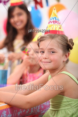 Little Girl And Her Friends At A Birthday Party Stock Photo