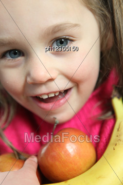 Little Girl Holding Apples And Banana Stock Photo