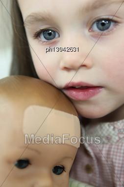 Little Girl Holding Doll Stock Photo