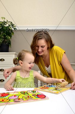 Little Girl And Mom Playing In A Children Puzzle Stock Photo