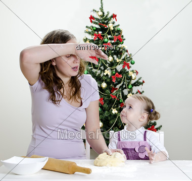 Little Girl And Mother Are Preparing Christmas Cookies, Mom Seems To Be Tired Stock Photo