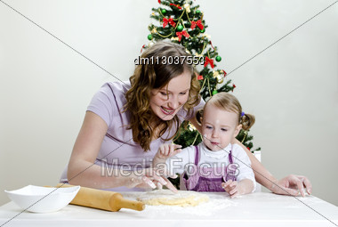 Little Girl And Mother Are Preparing Christmas Cookies Stock Photo