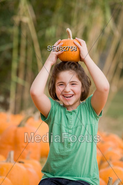 Little Girl Playing in Pumpkin Patch Stock Photo