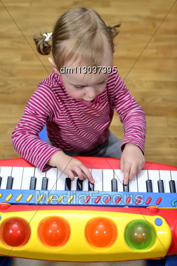 Little Girl Playing The Piano Stock Photo