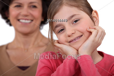 Little Girl Posing With Mother All Smiles In Background Stock Photo