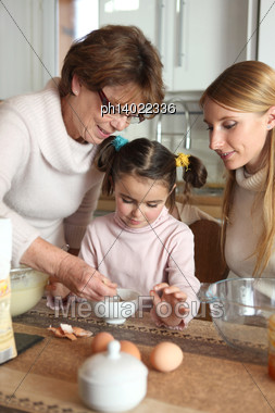 Little Girl Preparing Cake With Her Mother And Her Grandmother Stock Photo