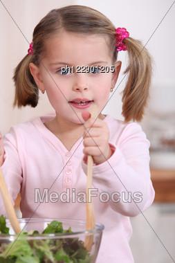 Little Girl Preparing Salad Stock Photo