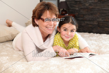 Little Girl Reading A Book With Her Granny Stock Photo