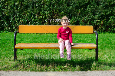 Little Girl Sitting On The Bench In The Park Stock Photo