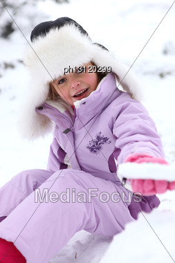 Little Girl Sitting On The Snow Stock Photo