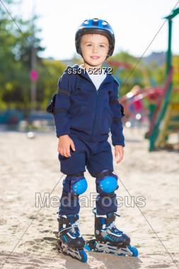 Little Skater Boy In Helmet Posing On The Playground Stock Photo