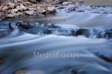 Long Exposure Of Water Flowing Down The River Stock Photo