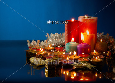 Lot Of Burning Colorful Candles Against Dark Blue Background Stock Photo