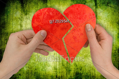 Love And Divorce. Two Hands Holding Broken Heart Stock Photo