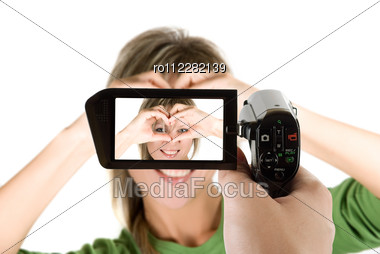 Lovely Blond Girl With Hands As Heart At Camcorder Stock Photo
