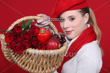 Lovely Blonde Carrying Basket Filled With Red And Dressed To Match Stock Photo