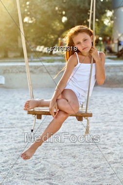 Lovely Little Girl Sitting On A Swing Outdoors Stock Photo