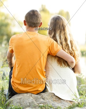 Lovers hugging and sitting on a stone in the nature. Stock Photo