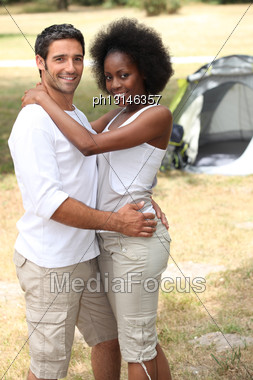 Loving Couple Hugging In Front Of Their Tent Stock Photo