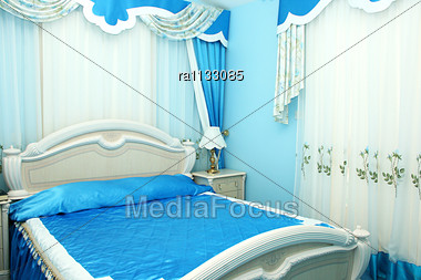 Luxurious Blue Bedroom With Beautiful Curtains. Stock Photo