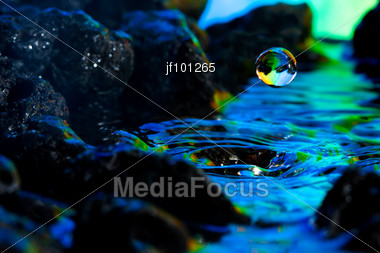 Macro Of Colorful Water Drop & Rocks Stock Photo