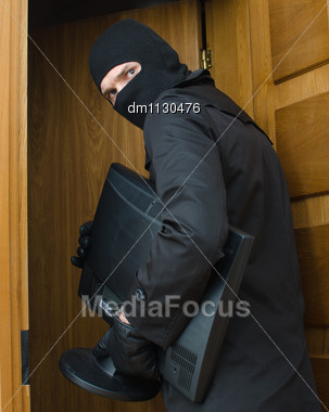 Male Burglar In Mask Breaking Into The House And Stealing Monitor Stock Photo