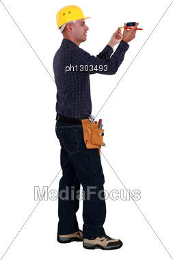Male Construction Worker Taking Measures. Stock Photo