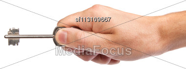 Male Hand Holding A Key To The House, Image Is Taken Over A White Background Stock Photo