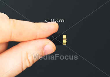 Male Hand Holding Micro SD Card On Black Background Stock Photo