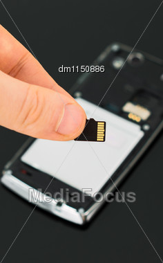 Male Hand Holding Micro SD Card Near Mobile Phone Stock Photo