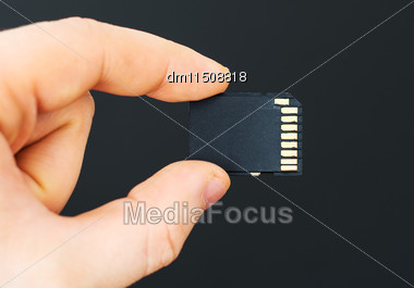 Male Hand Holding SD Card On Black Background Stock Photo