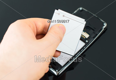 Male Hand Inserting Battery To Mobile Phone Stock Photo