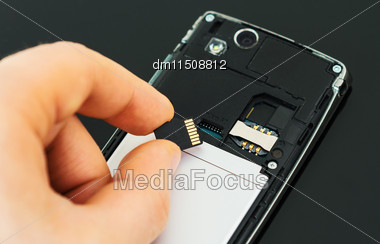 Male Hand Inserting Micro SD Card To Mobile Phone Stock Photo