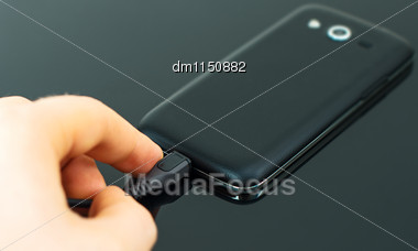 Male Hand Inserting Micro USB To Mobile Phone Stock Photo
