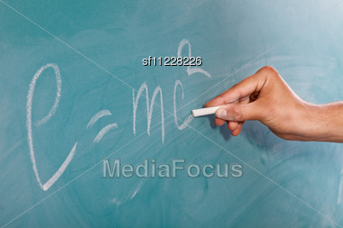 Male Hand Is Writing Einstein's Formula E=mc2 On A Blackboard Stock Photo