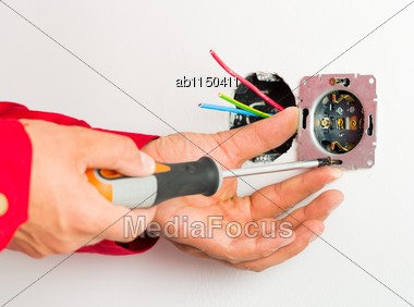 Male Hand Mounting New Electrical Outlet On Wall Stock Photo