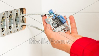 Male Hand Mounting New Electrical Outlet On Tiled Wall Stock Photo