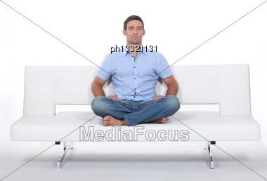 Man Alone On White Sofa Stock Photo