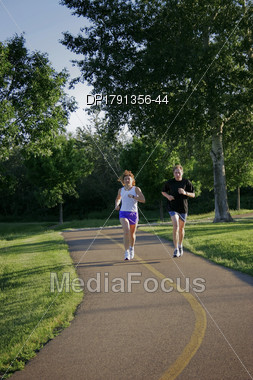 Man And Woman Jogging On Trail Stock Photo