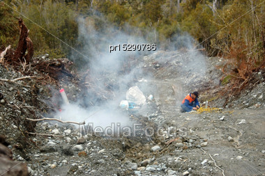 Man Blows Up A 4 Metre Deep Charge For Seismic Test, Westland, New Zealand. Smoke Emerges From The Blast Site Stock Photo