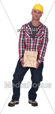 Man Carrying Pile Of Bricks Stock Photo