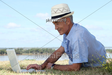 Man With Computer At Edge Of River Stock Photo