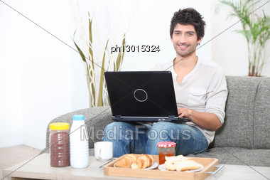 Man Doing Computer At Breakfast Stock Photo
