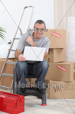 Man Doing Computer In A Room Full Of Cardboards Stock Photo