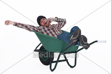 Man Dozing In A Wheelbarrow Stock Photo