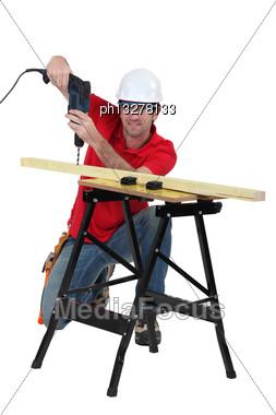 Man Drilling Through Plank Of Wood Stock Photo