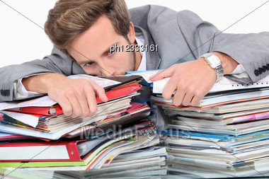 Man Drowning In Stacks Of Paperwork Stock Photo