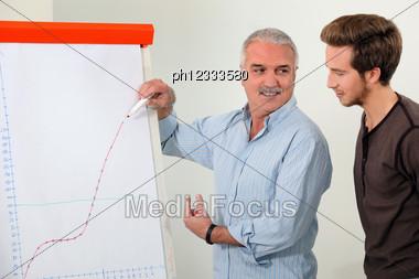 Man Explaining A Growth Chart Stock Photo