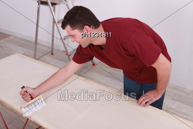 Man Gluing Paper Stock Photo