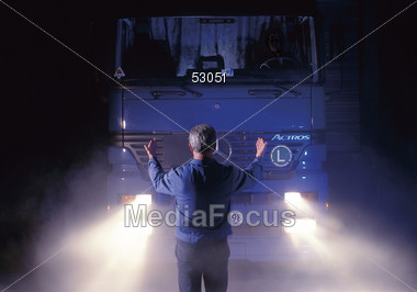 Man Guiding In Delivery Truck At Night Stock Photo